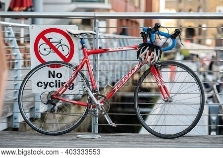 London, Uk - November 2, 2020: Red Bike Leaning Against A No Cycling Sign On Metal Railings.