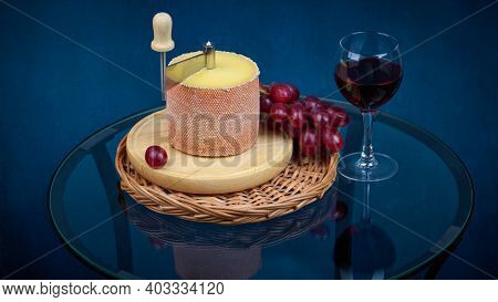Gourmet Tasty Cheese Tete De Moine, A Glass Of Red Wine And A Bunch Of Grapes On A Glass Table, Shal