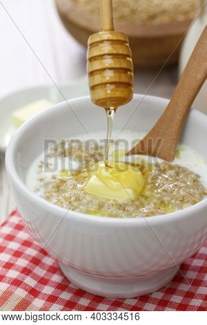 dropping honey by wooden dipper on Scottish porridge with milk and butter.