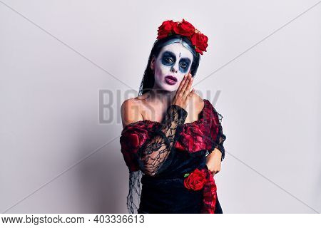 Young woman wearing mexican day of the dead makeup hand on mouth telling secret rumor, whispering malicious talk conversation