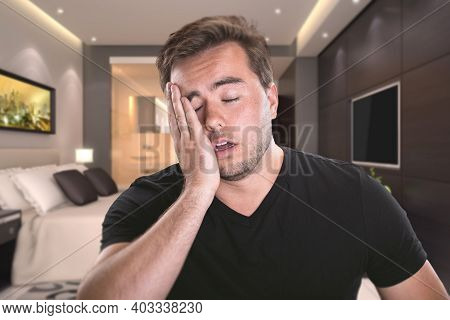 Man feeling sick inside a hotel room or at home.  He is in quarantine because of illness like covid,