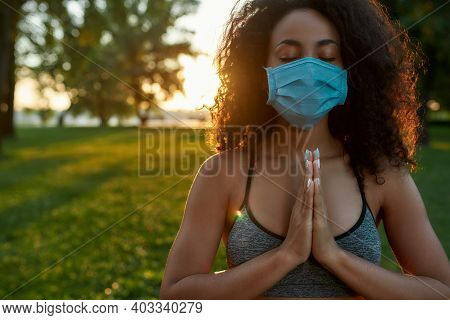 Sport And Covid 19. Young Mixed Race Woman Wearing Protective Face Mask Meditating And Practicing Yo