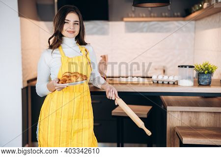 Smiling Young Beautiful Woman Girl With Apron Holding A Plate Of Fresh Tasty Croissant In Homey Kitc