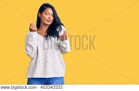 Hispanic woman with long hair wearing casual clothes doing money gesture with hands, asking for salary payment, millionaire business