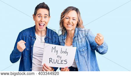 Couple of women holding my body my rules banner screaming proud, celebrating victory and success very excited with raised arms