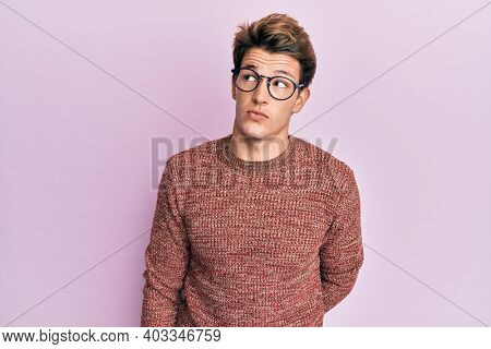 Handsome caucasian man wearing casual sweater and glasses smiling looking to the side and staring away thinking.