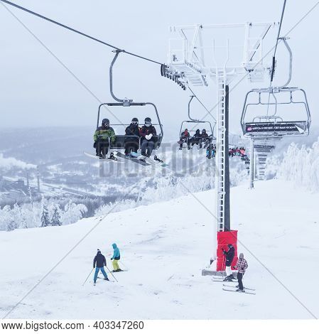 Perm Krai, Russia - January 02, 2021: Skiers Skiing Downhill And Taking A Chair Lift In A Hilly Wint