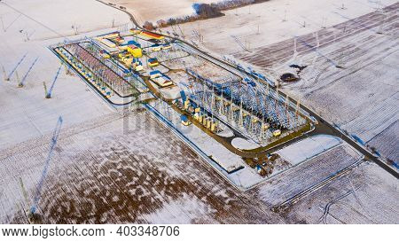 High voltage substation in snowy field. It is a part of an electrical generation, transmission, and distribution system in Central Europe.