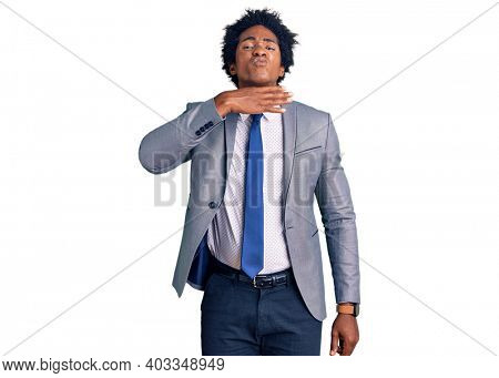 Handsome african american man with afro hair wearing business jacket cutting throat with hand as knife, threaten aggression with furious violence
