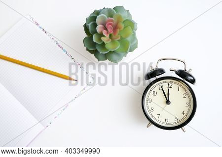 Alarm Clock Showing 5 Minutes To Twelve And A Notebook With A Yellow Pencil On White Table, As A Con