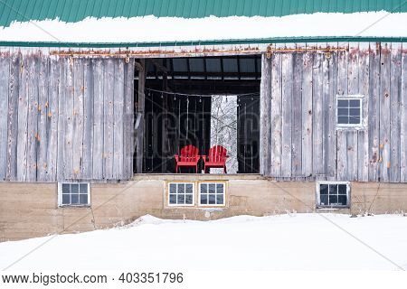 Two Red Adirondack Chairs Sitting In A Barn Door, In Winter
