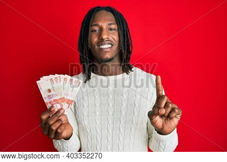 African american man with braids holding 10 colombian pesos banknotes smiling with an idea or question pointing finger with happy face, number one