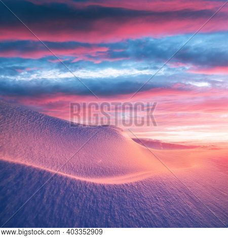 Fantastic winter landscape in snowy mountains glowing by morning sunlight. Dramatic wintry scene with frozen snowy hills at sunrise. Christmas holiday background