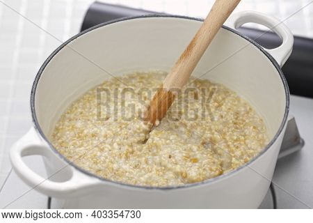making traditional Scottish porridge by wooden spurtle