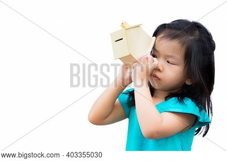 Girl Is Looking In A Wooden House Piggy Bank. Children Look For Money In Wooden House. Child Pick Up