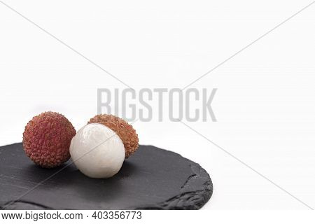 Opened And Unpeeled Lychee Fruit On A Black Slate Tray On White Background