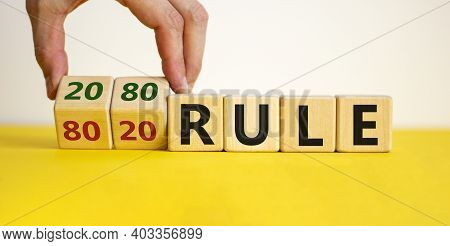 80 On 20 Rule Symbol. Male Hand Flips Wooden Cubes With Words '80 On 20 Rule'. Beautiful Yellow Tabl