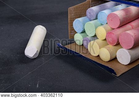 School Chalk On A Black Blackboard. Accessories For Lectures And Lessons At School. Dark Background.