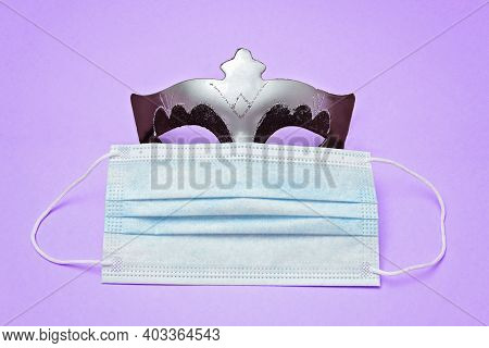Purim Carnival Mask And Medical Face Mask On Violet Background. Coronavirus Protection Minimal Conce