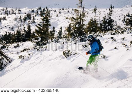 Guy In Bright Suit Rides Freeride On A Snowboard