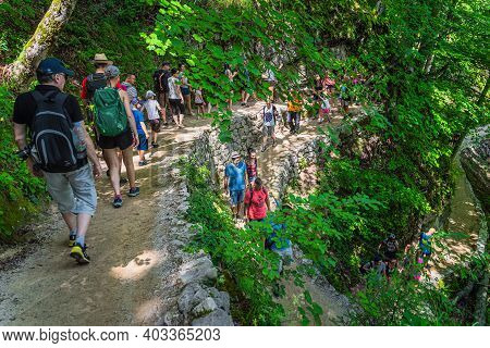 Plitvicka Jezera, Croatia, July 2019 Crowds Of Tourists On Winding Footpath In Green Lush Forest Of
