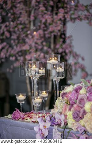 Patio Wedding Dining Setting With Flower Arrangements, Candles And Decor In A Patio With Flowering T