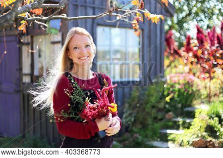 A Happy, Smiling Woman Gardener Is Holding Flowers Outside Her Cottage Garden And Shed.