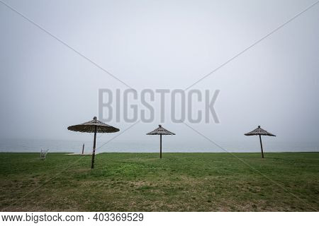 Smoggy Fog In Winter On The Palic Lake, In Subotica, Serbia, While Sun Umbrella Parasols Are Visible