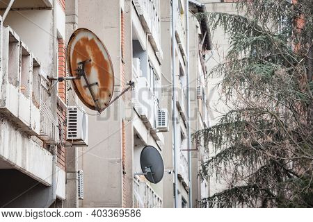Rusty Satellite Dish Tv Uhf Antennas On Display At The Top Of A Traditionnal Communist Housing In Th
