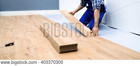 Worker Installing Home Floor. Carpenter Laying Laminate Flooring