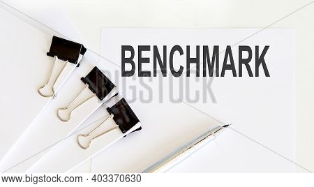 Benchmark Written On White Page With Office Tools