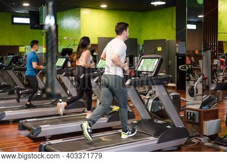 Group Of People Running On Treadmills In Modern Sport Gym. High Quality Photo