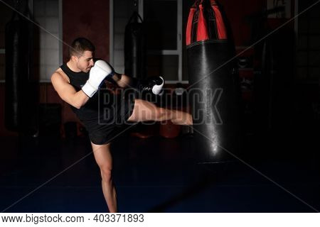 Muscular Handsome Kickboxing Fighter Giving A Forceful Kick During A Practise Round With A Boxing Ba
