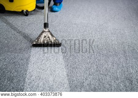 Professional Carpet Cleaning Service. Vacuum Cleaner. Janitor Removing Stain