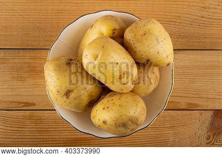 Raw Potatoes With Peel In White Bowl On Wooden Table. Top View