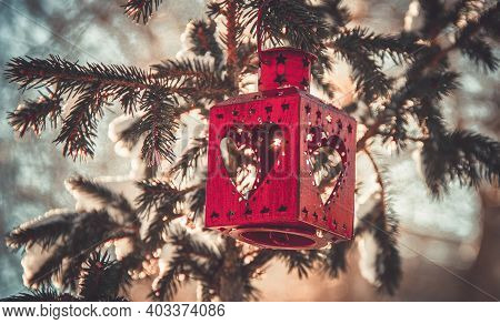 Red Christmas Lantern Hangs On A Snow-covered Christmas Tree