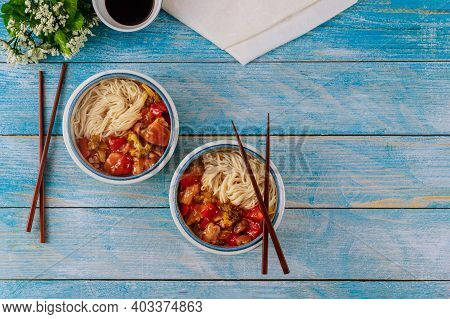 Rice Noodles With Stir-fried Chicken And Vegetables In Bowls And Chopsticks. Top View.