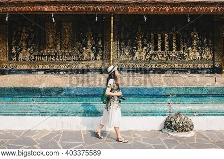 Portrait Of Young Asian Tourist Visiting Wat Xieng Thong An Iconic Temple In Luang Prabang, The Unes