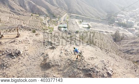 Man Riding Mountain Bikes Along The Barren Rocky Terrain