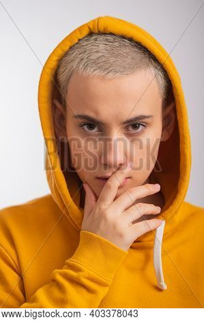 Young Woman In Ocher Hood Covers Her Face With Hand On White Background.