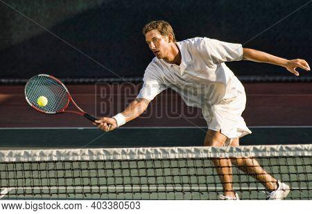 Portrait of man hitting tennis ball in court match
