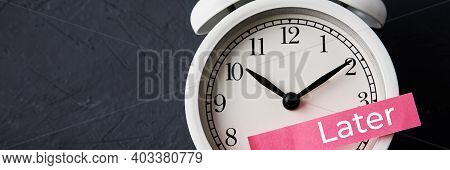 Procrastination And Delay Concept. Sticky Note With Word Later On The White Alarm Clock. Urgency Tim