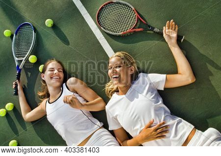 Exhausted women lying on tennis court after playing