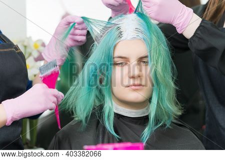 Two Hairdressers Use Pink Brush When Applying Paint To Hair During Process Of Bleaching Hair Roots.