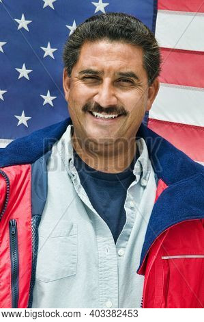 Photo of mexican middle aged man standing against american flag
