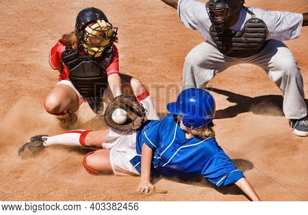 Softball player sliding into home plate while umpire rules safe