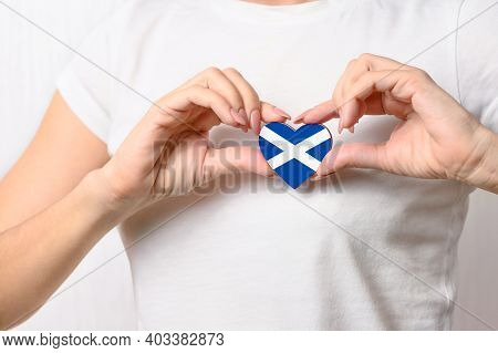 Love Scotland. The Girl Holds A Heart In The Form Of The Flag Of Scotland On Her Chest. Scottish Pat