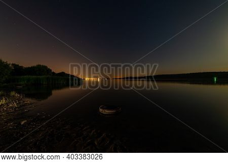 Lake Or River Sand Shore With Trees And Dark Blue Starry Sky And City Light On Background. Tranquil