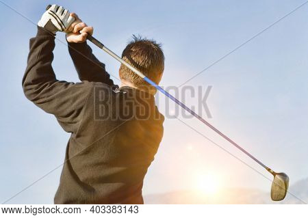 Rear shot of Male golfer Swinging Golf Club