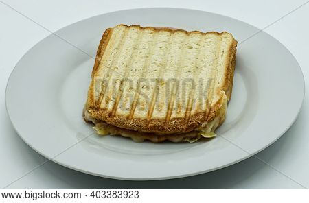Toast Bread Sandwich Ham With Melted Tilsiter Cheese On White Dish, Isolated On White Background